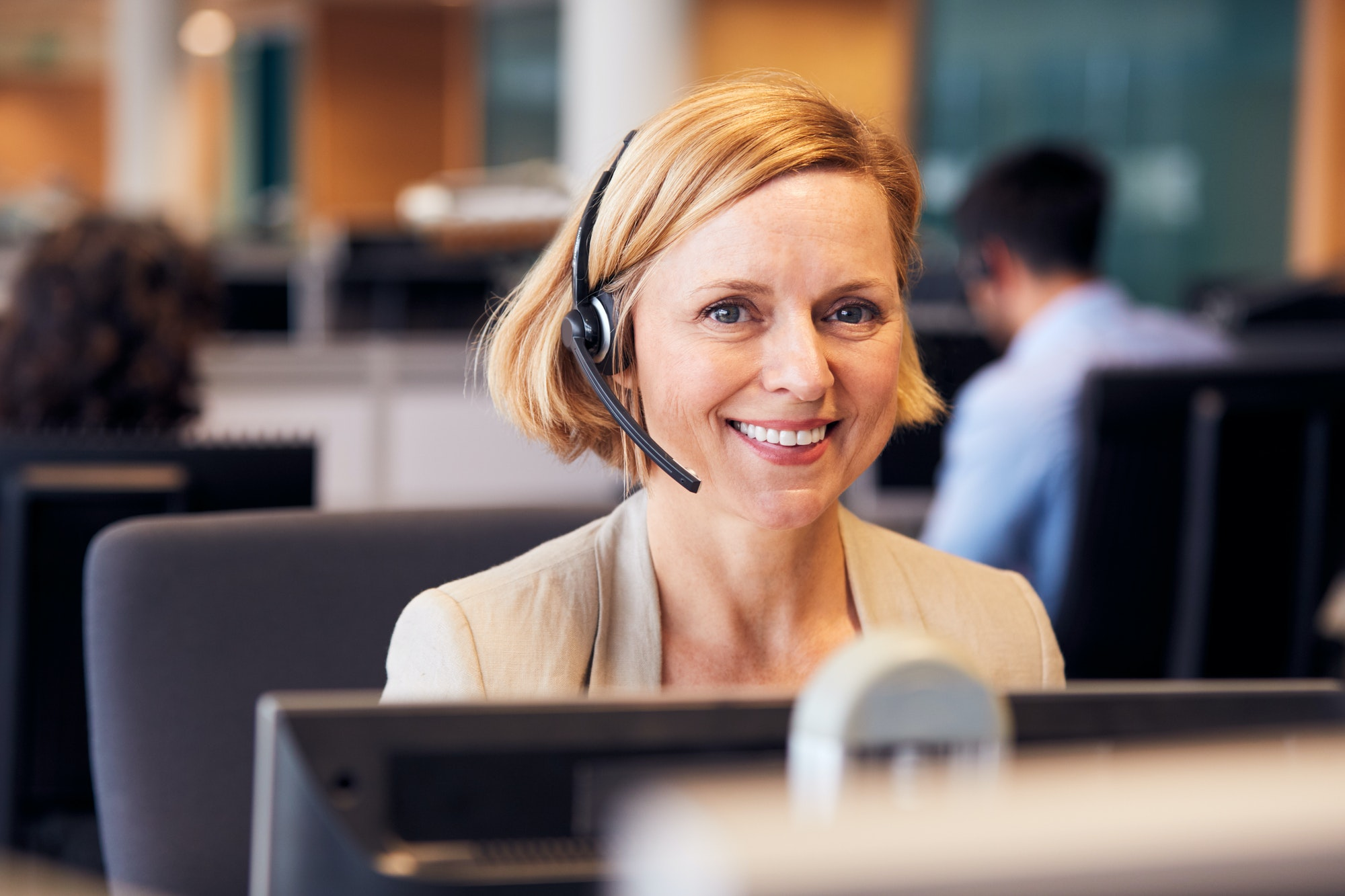 Portrait Of Mature Businesswoman Wearing Telephone Headset Working In Customer Services Department