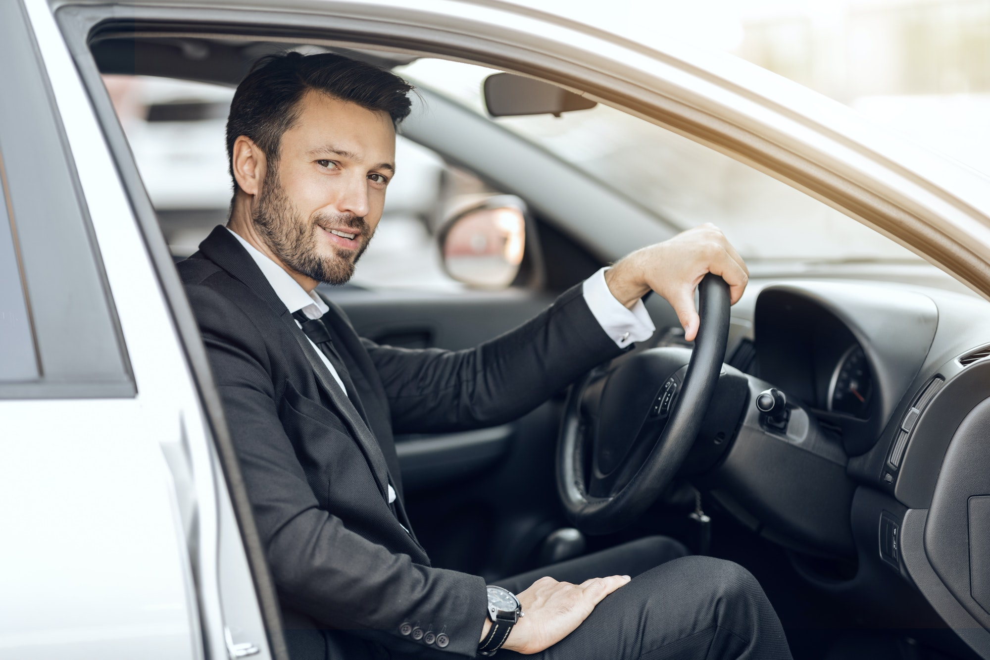 Happy young entrepreneur sitting in car, driving to office